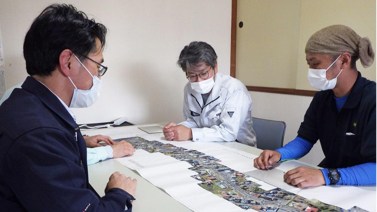 現場の図面を見ながらインタビューに答える江藤工事次長(右奥)と堀内さん(右手前)
